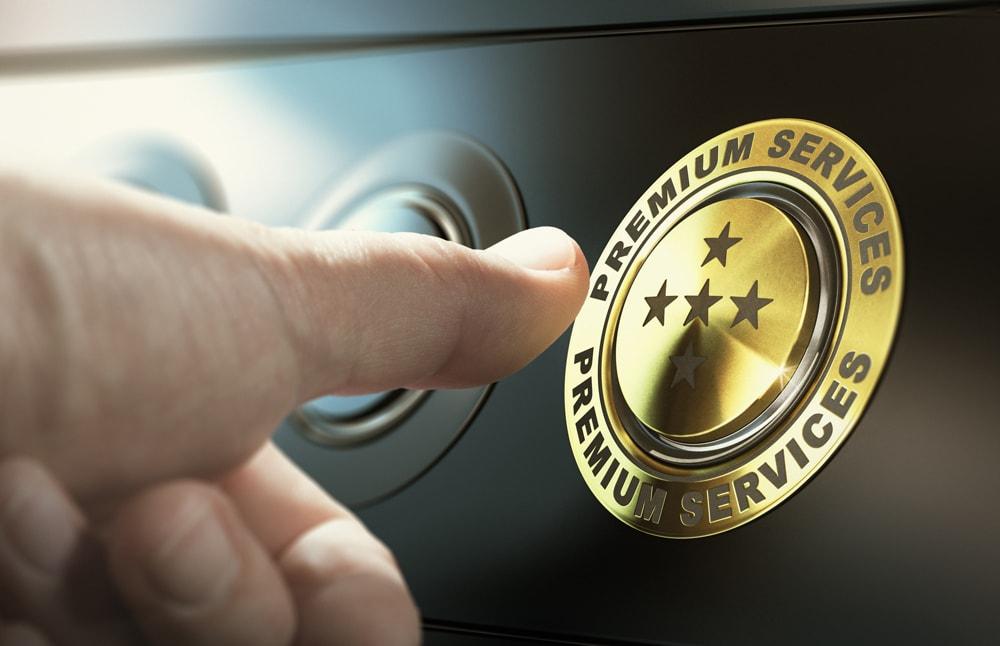 """image d'un bouton avec écrit au tour """"service premium"""" sur lequel le pouce d'une personne s'apprête à appuyer"""